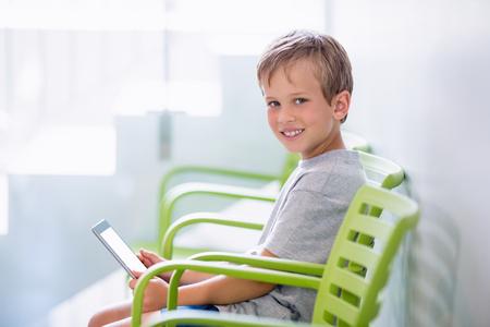 Portrait of boy sitting on chair using digital tablet in corridor at hospital