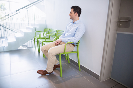 Smiling man sitting on chair in hospital corridor