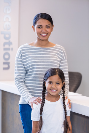 Portrait of smiling mother and daughter standing at counter in hospital Stock Photo