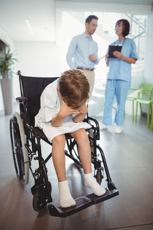 afflict: Sad disable boy in wheelchair in corridor at hospital Stock Photo