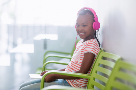 Portrait of girl listening to music from digital tablet in hospital Stock Photo