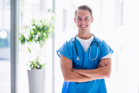 iv: Portrait of smiling doctor standing with arms crossed in hospital Stock Photo