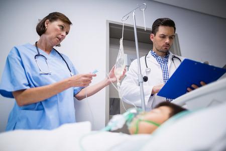 paciente en camilla: Doctors adjusting iv drip while patient lying on bed in hospital corridor