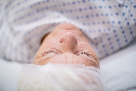 treating: Senior woman patient sleeping on bed in hospital room