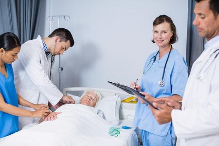 paciente en camilla: Doctors examining patient in ward at hospital Foto de archivo