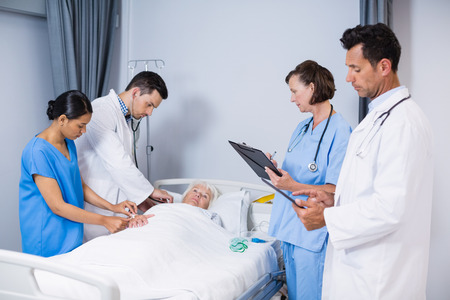 Doctors examining patient in ward at hospital Stock Photo