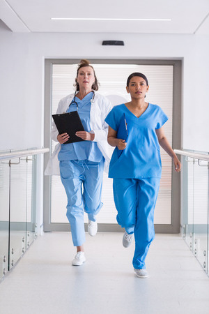 Nurse and doctor running in hospital corridor