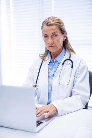 the sixties: Portrait of female doctor using laptop in clinic Stock Photo