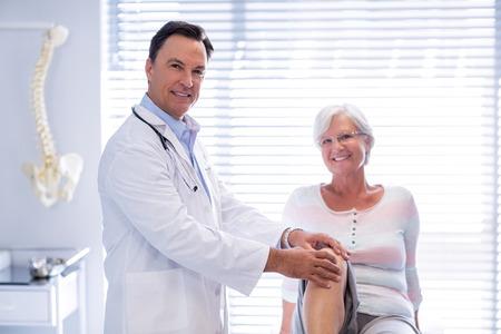 클리닉의 수석 여자에게 무릎 치료를주는 물리 치료사의 초상화 스톡 콘텐츠