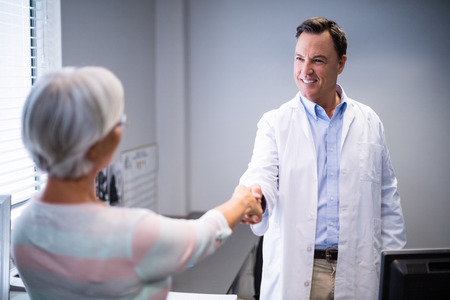 old man on a physical pressure: Doctor shaking hands with senior woman in clinic