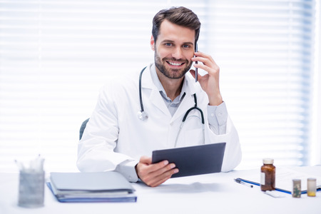 Male doctor talking on mobile phone while using digital tablet in clinic Stock Photo