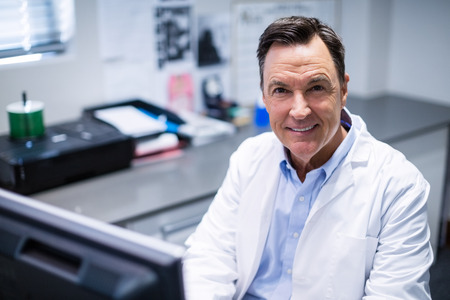 old man on a physical pressure: Portrait of male doctor smiling in clinic
