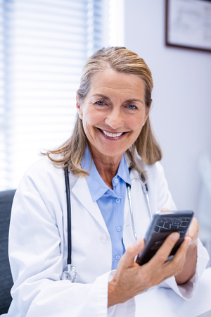 Portrait of female doctor using mobile phone in clinic Stock Photo