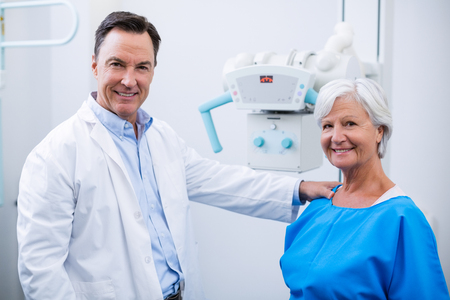 radiotherapy: Portrait of smiling doctor and senior woman during medical check-up in hospital Stock Photo