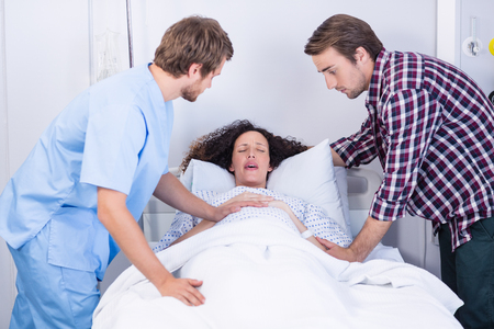 Doctor and man comforting pregnant woman in ward of hospital