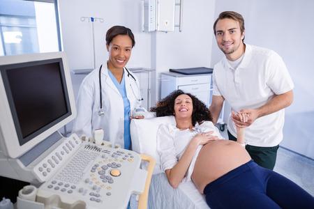 Hombre consolando a la mujer embarazada durante el ultrasonido en el hospital