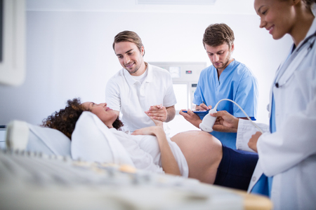Doctor doing ultrasound scan for pregnant woman in hospital Stock Photo