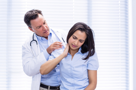 Female patient showing neck pain to doctor in clinic