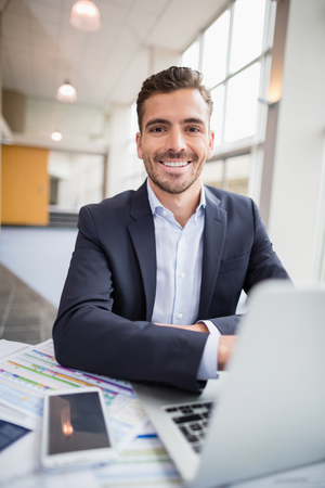 conference centre: Happy businessman using laptop at desk in conference centre