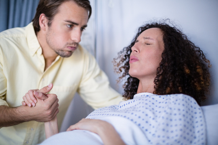 Man comforting pregnant woman during labor in ward of hospital