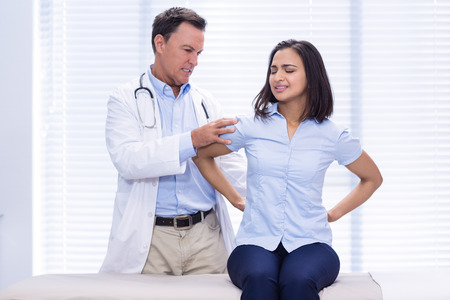 Female patient showing back pain to doctor in clinic