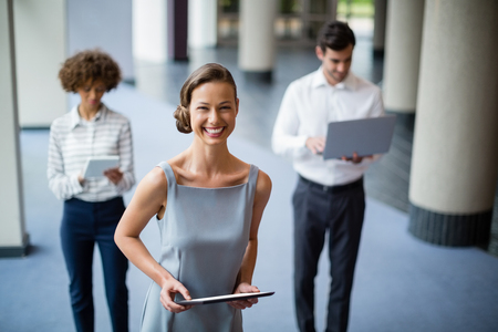company premises: Portrait of cheerful businesswoman holding digital tablet at conference centre