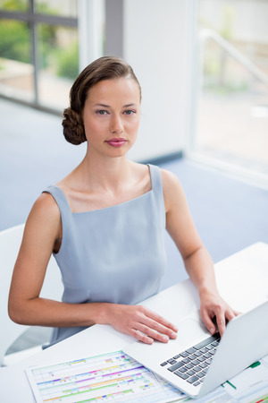 premises: Portrait of businesswoman sitting with laptop at conference centre