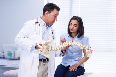 물리 치료사가 병원에서 척추 모델을 환자에게 설명합니다.