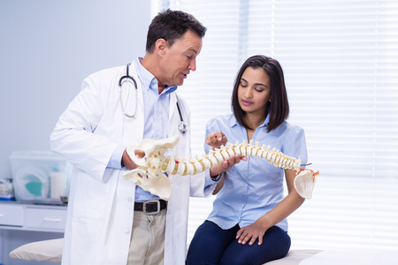Physiotherapist explaining spine model to patient in clinic