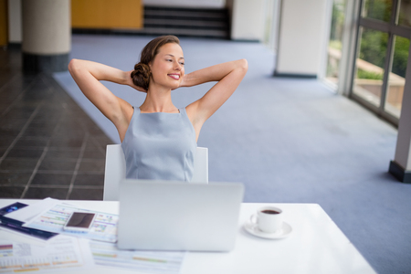 Happy businesswoman relaxing at desk in conference centre