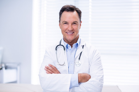 Portrait of male doctor standing with arms crossed in clinic