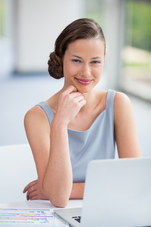 Portrait of businesswoman sitting with laptop at conference centre