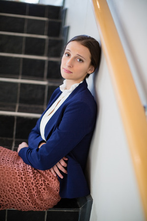 company premises: Portrait of worried businesswoman sitting on steps at conference centre