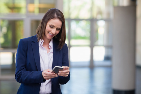 conference centre: Businesswoman using mobile phone at conference centre