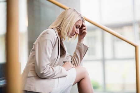 premises: Worried businesswoman sitting on steps at conference centre
