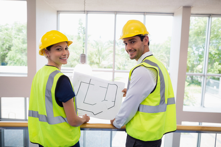 conference centre: Portrait of architects holding a blueprint at conference centre