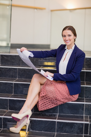 Portrait of a businesswoman sitting on steps holding blueprint