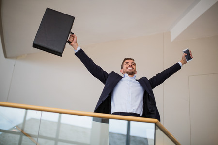company premises: Happy businessman holding a briefcase and mobile phone cheering