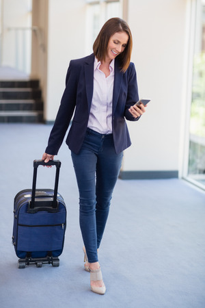 premises: Businesswoman carrying luggage and using mobile phone at conference centre Stock Photo