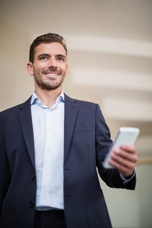 conference centre: Happy businessman holding a mobile phone at conference centre Stock Photo