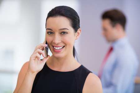 conference centre: Portrait of businesswoman talking on mobile phone at conference centre Stock Photo