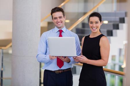 company premises: Portrait of happy business executives holding a laptop