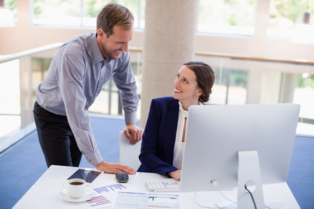 conference centre: Businesswoman working at desk with colleague in conference centre