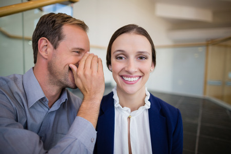 premises: Businessman whispering something to his colleague at conference centre Stock Photo