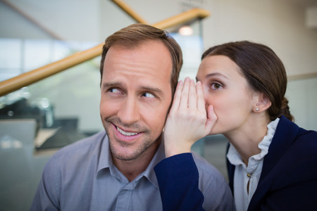 premises: Businesswoman whispering something to her colleague at conference centre