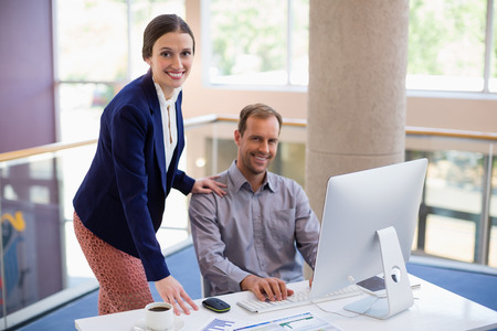 Businessman interacting with colleague at desk in conference centre