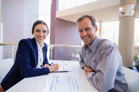 company premises: Portrait of business executives sitting at desk with document