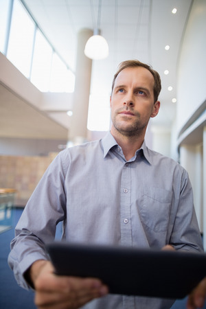 conference centre: Businessman holding a digital tablet at conference centre Stock Photo