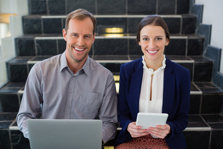 company premises: Portrait of businessman and woman sitting on steps holding laptop at conference centre