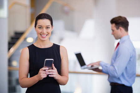 company premises: Portrait of businesswoman using mobile phone at conference centre Stock Photo